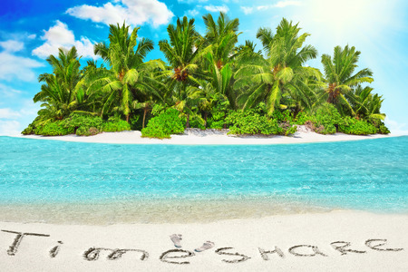 uninhabited: Whole tropical island within atoll in tropical Ocean. Uninhabited and wild subtropical isle with palm trees. Inscription TimeShare in the sand on a tropical island,  Maldives. Stock Photo