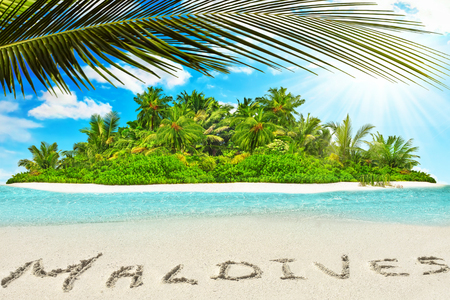 Whole tropical island within atoll in tropical Ocean. Uninhabited and wild subtropical isle with palm trees. Inscription Maldives in the sand on a tropical island,  Maldives.
