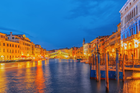 Rialto Bridge (Ponte di Rialto) or Bridge of Sighs and view of the most beautiful canal of Venice - Grand Canal and boats, gondolas, mansions along. Night view. Italy.