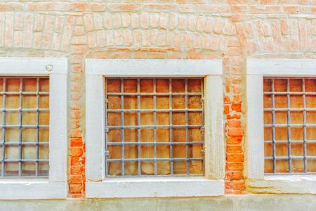 Drie vensters in de oude stad en de textuur van een bakstenen muur maakten van oude rode bakstenen. Beeld dat in Venetië wordt genomen.