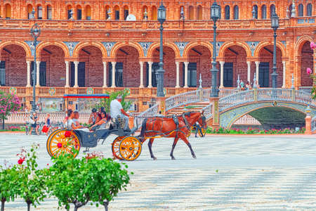 Seville, Spain - June 09, 2017 : Carriage with tourists on Spain Square (Plaza de Espana)  is a square built in 1928 for the Ibero-American Exposition of 1929.