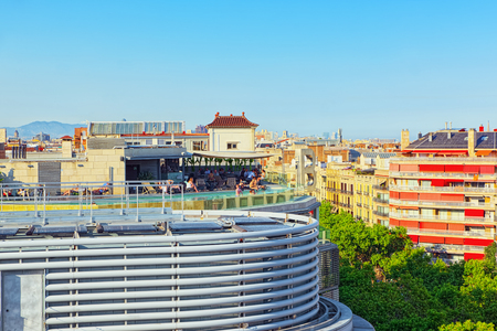 Barcelona, Spain - June 12, 2017 : Panorama on the urban center of Barcelona, the capital of the Autonomy of Catalonia. Pool on the roof with people.