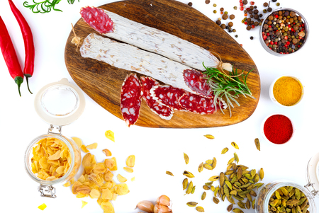 Sliced cured sausage with spices and a sprig of rosemary. Isolated on white.