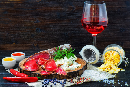 Sliced cured bresaola with spices and a glass of red wine on dark wooden rustic background.