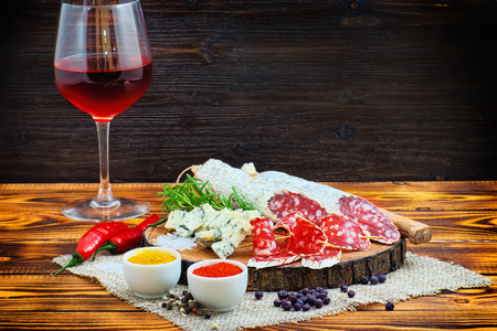 Sliced cured sausage with spices and a glass of red wine on dark wooden rustic background. Stock Photo