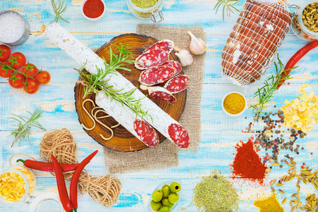 Sliced cured sausage with spices and a sprig of rosemary on blue wooden rustic background.