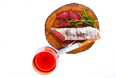 Sliced cured bresaola with a sprig of rosemary for a glass of wine. Isolated on white. Archivio Fotografico
