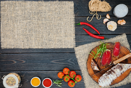 Sliced cured bresaola with spices and a sprig of rosemary on dark wooden rustic background. Stok Fotoğraf