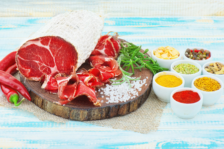 Sliced cured coppa with spices and a sprig of rosemary on wooden rustic background. Stock Photo