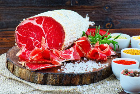 Sliced cured coppa with spices and a sprig of rosemary on dark wooden rustic background.