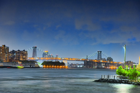 New York night view of the Lower Manhattan and the Manhattan Bridge across the East River. USA.