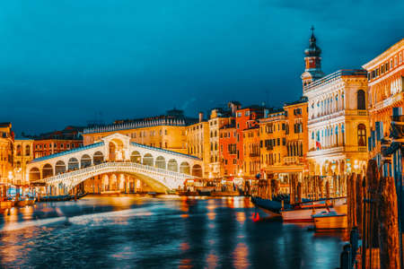 Rialto Bridge (Ponte di Rialto) or Bridge of Sighs and view of the most beautiful canal of Venice - Grand Canal and boats, gondolas, mansions along. Night view. Italy. Stockfoto