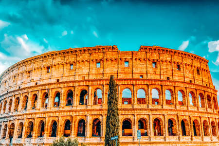ROME, ITALY- MAY 07, 2017: Beautiful landscape of the Colosseum in Rome- one of wonders of the world with tourist near it in the evening time.