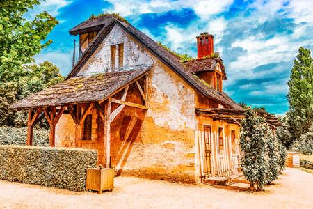 VERSAILLES, FRANCE - JULY 02, 2016 :Landscape of hamlet Queen Marie Antoinette's estate near Versailles Palace. Palace Versailles -most beautiful palace in France.