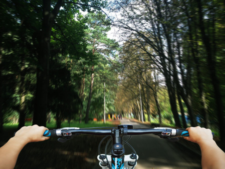handlebars: Mountain biking down hill descending fast on bicycle. View from bikers eyes.