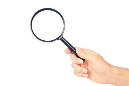 Hand holding magnifying glass on white backckground