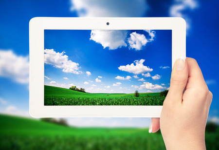 tablet computer in hand on the field backgrounds photo