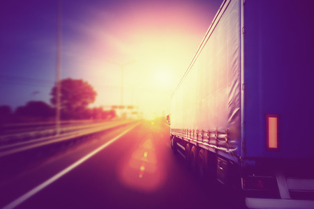 Semi Truck In Motion. Speeding Truck on the Highway Stock Photo