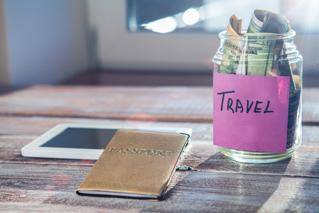 holiday budget: objects for travel isolated on a wooden background