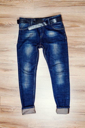 trouser: Jeans trouser over dark wood planks background