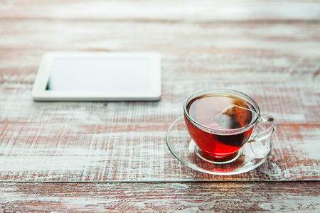tea table: red tea with a tablet on a table in an office