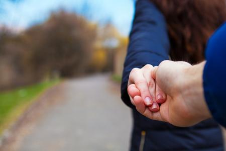 Una chica va en un poste que sostiene un compañero en una mano Foto de archivo - 56257819