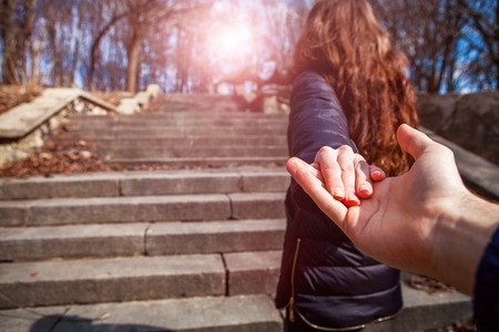 Une fille va sur un poteau tenant un camarade sur une main Banque d'images - 56257874