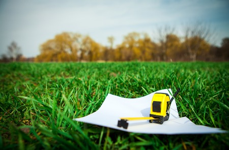 Papers and tape-measure with pencil on green grass in the park