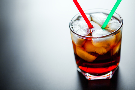 carbonation: soft drinks. Cola glass with ice cubes on a white background