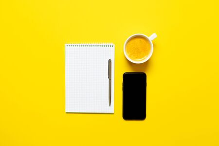 Top view of business working place with cup of coffee, Empty workspace on yellow table background. Banque d'images - 135491770