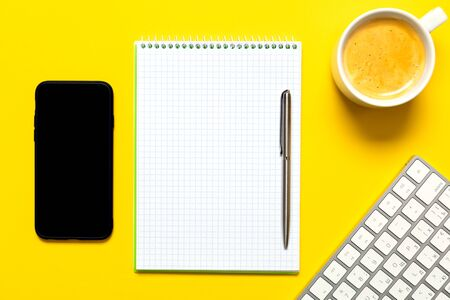 Top view of business working place with cup of coffee, Empty workspace on yellow table background. Banque d'images - 135491859