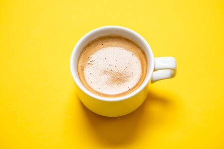 Black coffee in a cup on a yellow background Banque d'images - 135490871