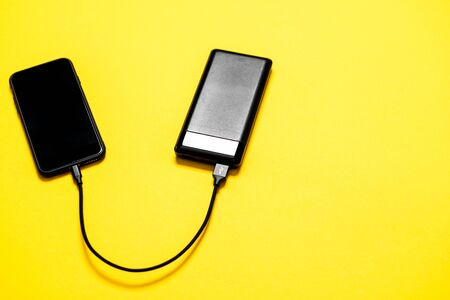 Black Power bank charges smartphone isolated on yellow background Banque d'images - 135491851
