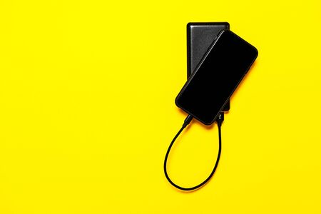 Black Power bank charges smartphone isolated on yellow background Banque d'images - 135491904