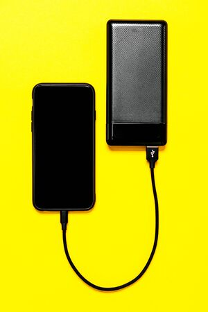Black Power bank charges smartphone isolated on yellow background Banque d'images - 135491907