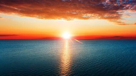 Aerial view of sun rising over sea. Banque d'images - 135493214