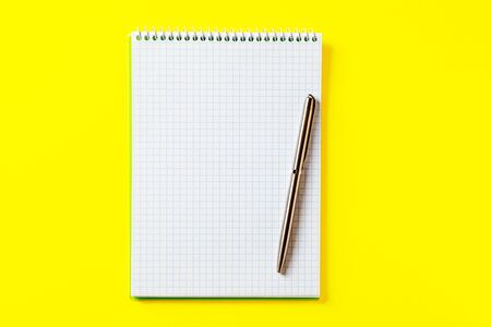 the white open notepad on silver pen isolated on the yellow background Banque d'images - 135493370