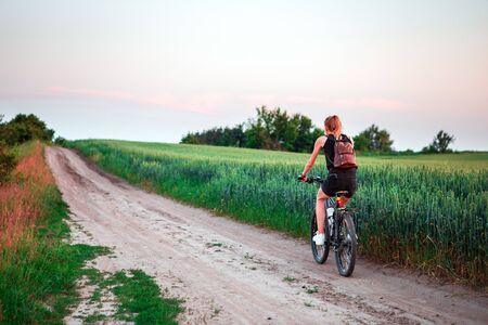 woman on a green meadow riding a bicycle Zdjęcie Seryjne