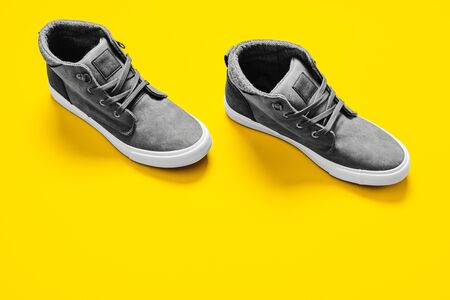 Man fashion gray boots isolated on yellow background.