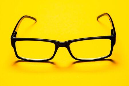 black eye glasses isolated on yellow background