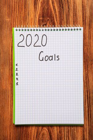 New year Concept Top view of 2020 goals on notebook on wood table background Banque d'images - 137370337