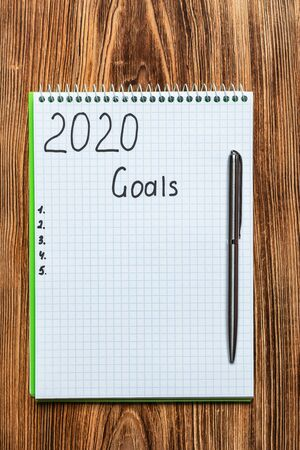 New year Concept Top view of 2020 goals on notebook on wood table background