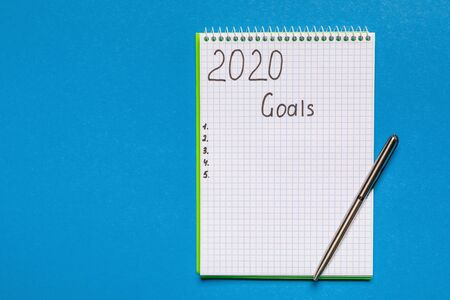2020 GOALS on his notebook. New year resolutions concept. Top view. isolated on blue background Banque d'images - 137370507