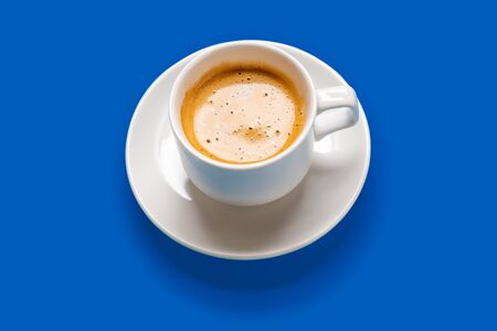 Black coffee in a cup on a blue background Banque d'images - 137370489