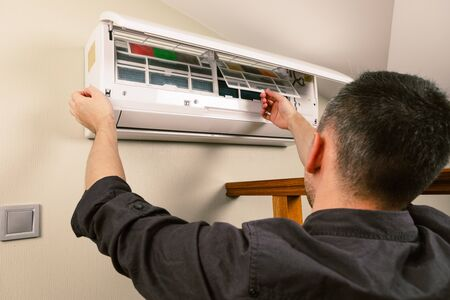 Male technician cleaning air conditioner indoors Banque d'images - 137371122