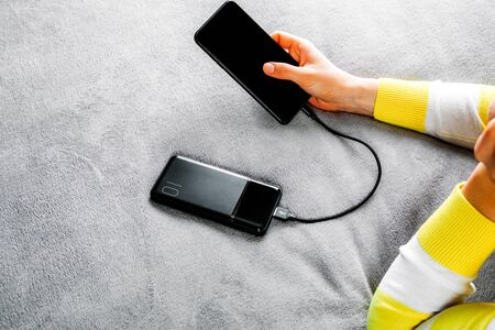 The woman plugged the charger with the phone in office or at home. Power Bank.
