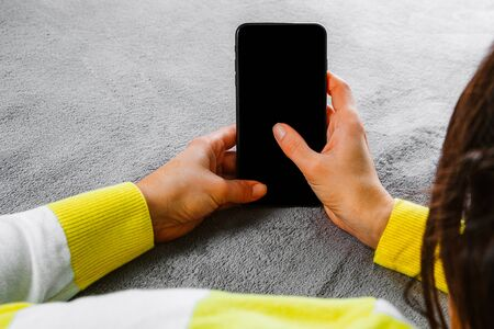 Woman lying on the bed and holding smartphone in hand.