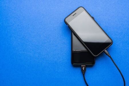 Black Power bank charges smartphone isolated on blue background Banque d'images