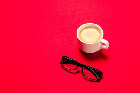 Cup of coffee and eye glasses isolated on red background. Office table concept. Top view with copy space. 免版税图像