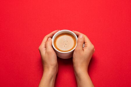 Female hand holding a white cup with black coffee on a red background. 免版税图像